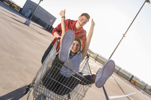 Playful young couple with shopping cart on parking level - UUF12295