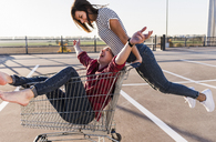 Playful young couple with shopping cart on parking level - UUF12298