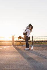 Young couple hugging on parking level at sunset - UUF12313