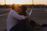 Young couple kissing on parking level at sunset - UUF12316