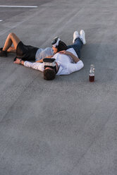 Young couple lying on parking level wearing VR glasses - UUF12319