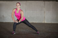 Smiling sportive woman stretching - ZEF14827