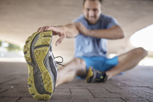 Sportive man sitting and stretching - ZEF14833