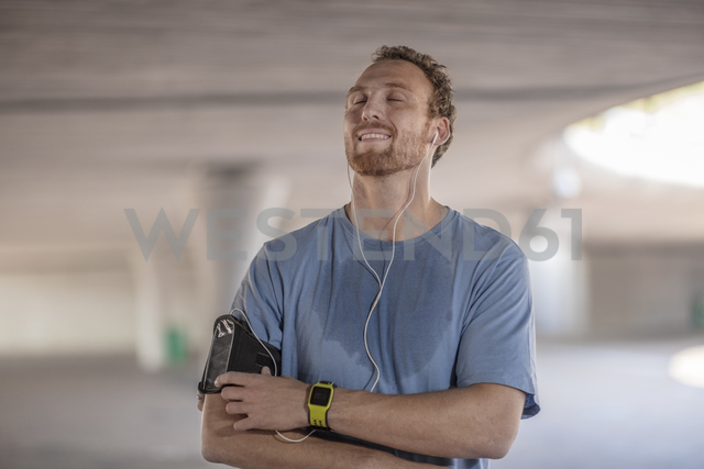 Man exercising and listening to music wearing earphones - ZEF14836