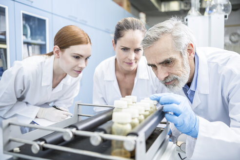Three scientists in lab examining samples - WESTF23685
