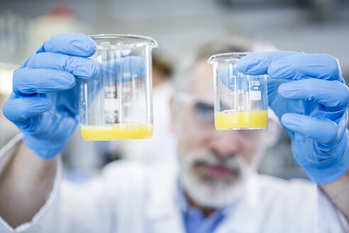 Scientist in lab holding up two beakers with liquid - WESTF23703