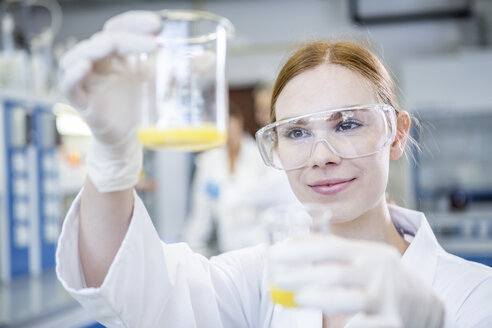 Scientist in lab holding up two beakers with liquid - WESTF23706