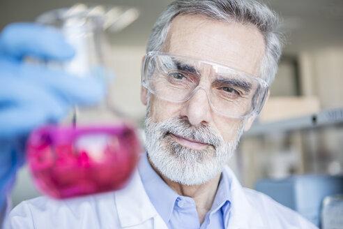 Scientist in lab holding beaker with liquid - WESTF23739