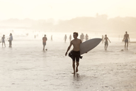 Indonesia, Bali, surfer carrying his surfboard on the beach at sunset - KNTF00917