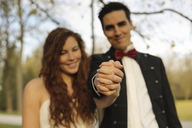 Happy bridal couple standing in park, holding hands, showing wedding ring - FCF01302