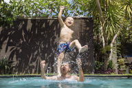 Father and son having fun in swimming pool - KNTF00932