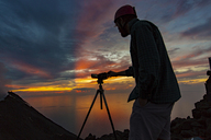 Italy, Aeolian Islands, Stromboli, young man observing volcanic eruption with colorful sunset background - THGF00026