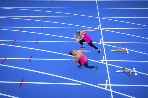Top view of two female runners starting on tartan track - STSF01424