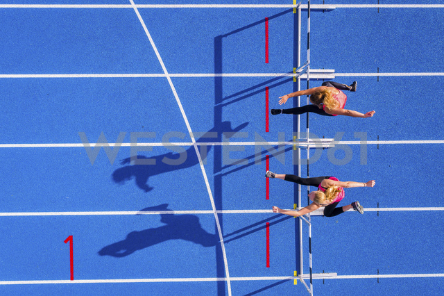 Top view of two female runners crossing hurdles on tartan track - STSF01427 - Stefan Schurr/Westend61