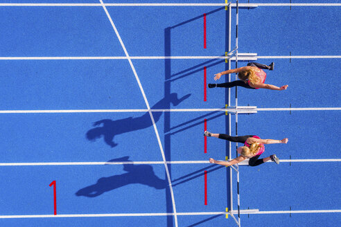 Top view of two female runners crossing hurdles on tartan track - STSF01427