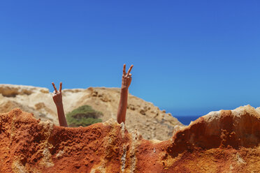 Woman doing victory sign behind rock at the beach - JPF00282