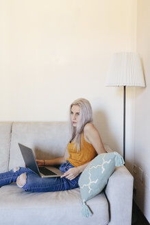 Young woman with laptop on couch at home - GIOF03353