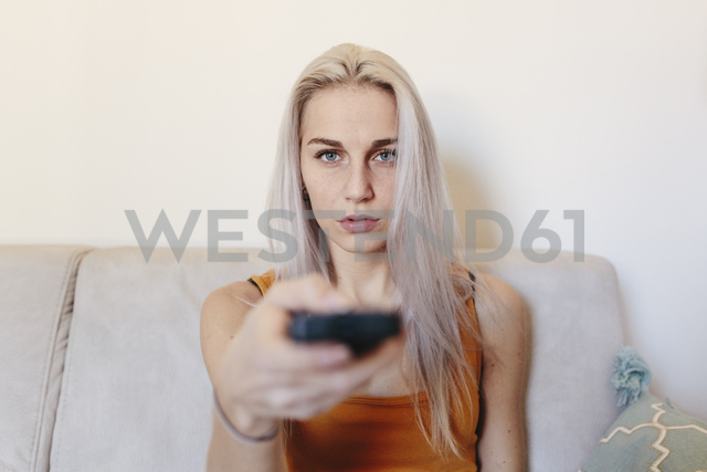 Young woman sitting on couch at home with remote control - GIOF03356
