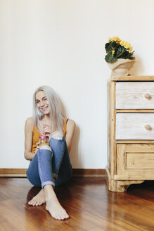 Smiling young woman sitting on the floor at home - GIOF03359