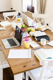 Laptop, books and notepads on a wooden table at home - GIOF03368