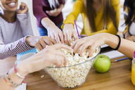 Friends taking popcorn from bowl at table at home - GIOF03389