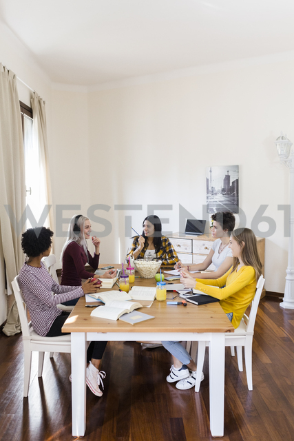 Group of female students working together at table at home - GIOF03410