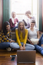 Group of female friends looking at laptop together at home - GIOF03416