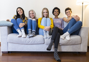 Portrait of group of female friends sitting on sofa in living room - GIOF03422