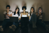Group of female friends at home sitting on floor using technology in the dark - GIOF03452
