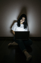 Young woman at home sitting on floor using laptop in the dark - GIOF03455