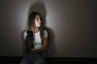 Young woman at home sitting on floor using cell phone in the dark - GIOF03458