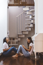 Two happy young women with cell phones sitting on the floor at home - GIOF03464