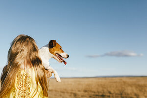 Girl holding dog at a field - JPF00283