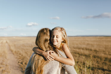 Smiling daughter hugging mother at a field - JPF00286