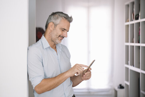 Smiling mature man using cell phone at home - ALBF00250