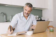 Smiling man writing in notebook and using laptop in home office - ALBF00253