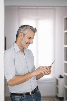 Smiling mature man using cell phone at home - ALBF00262