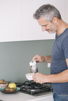 Mature man in kitchen pouring in cup of coffee - ALBF00265