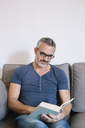 Mature man sitting on couch at home reading book - ALBF00271