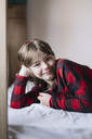 Portrait of smiling girl lying on bed - ALBF00284