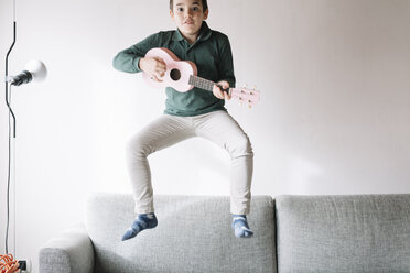 Portrait of boy with ukulele jumping in the air on the couch - ALBF00290