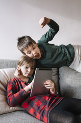 Girl lying on the couch in the living room using tablet while her brother interrupting - ALBF00302