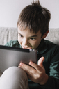 Portrait of laughing boy sitting on the couch in the living room using tablet - ALBF00305