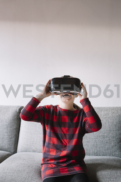 Girl sitting on the couch in the living room using Virtual Reality Glasses - ALBF00308 - Alberto Bogo/Westend61