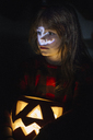Portrait of girl with lighted Jack O'Lantern at Halloween - ALBF00314