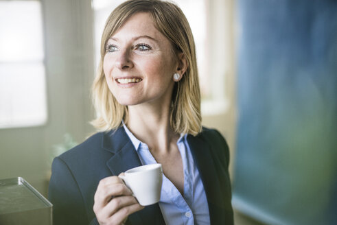 Smiling businesswoman holding espresso cup in office - JOSF01915