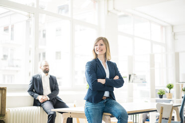 Smiling businesswoman and man in office - JOSF01918