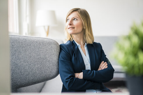 Smiling businesswoman sitting on couch in office lounge - JOSF01927