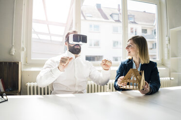 Woman and man with house model and VR glasses in office - JOSF01933