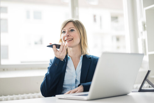 Smiling businesswoman in office using cell phone and laptop - JOSF01936